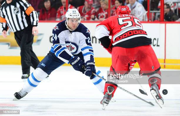 Grant Clitsome of the Winnipeg Jets tries to steal the puck from Chad LaRose of the Carolina Hurricanes during an NHL game on February 21 2013 at PNC...