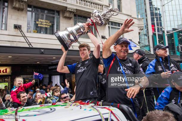 CEO Grant Dalton gestures while helmsman Peter Burling holds up the America's Cup yachting trophy as members of the Emirates Team New Zealand...