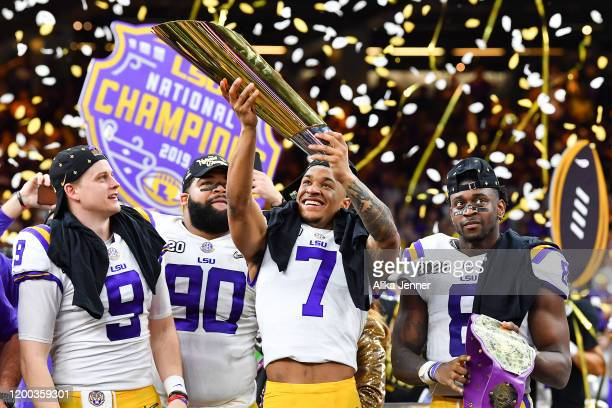 Grant Delpit of the LSU Tigers raises the National Championship Trophy with Joe Burrow left Rashard Lawrence and Patrick Queen after the College...