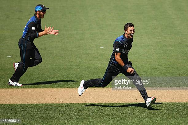 Grant Elliott and Trent Boult celebrate Boult taking the wicket of Mitch Marsh of Australia during the 2015 ICC Cricket World Cup match between...