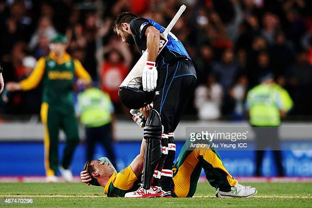 Grant Elliott of New Zealand gives a hand to help up a dejected Dale Steyn of South Africa after the 2015 Cricket World Cup Semi Final match between...