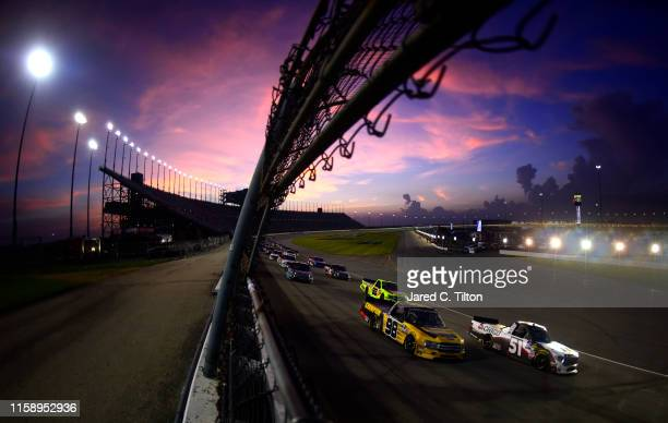 Grant Enfinger driver of the Champion Power Equipment Ford and Brandon Jones driver of the Chigo/Menards Toyota lead a pack of trucks during the...