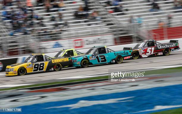 Grant Enfinger driver of the Champion Power Equipment Ford leads a pack of trucks during the NASCAR Gander Outdoors Truck Series Ultimate Tailgating...
