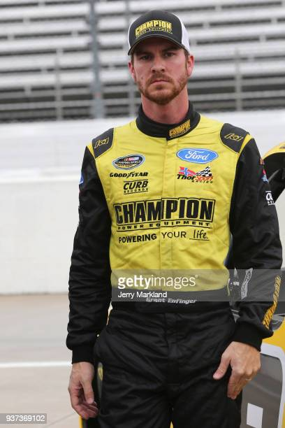 Grant Enfinger driver of the Champion Power Equipment/Curb Records Ford stands on the grid during qualifying for the NASCAR Camping World Truck...