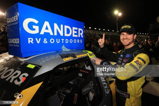 Grant Enfinger driver of the Champion/Curb Records Ford affixes the winner's decal on his car in Victory Lane after winning the NASCAR Gander RV...