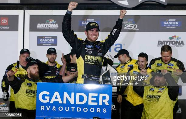 Grant Enfinger driver of the Champion/Curb Records Ford celebrates in Victory Lane after winning the NASCAR Gander RV Outdoors Truck Series NextEra...