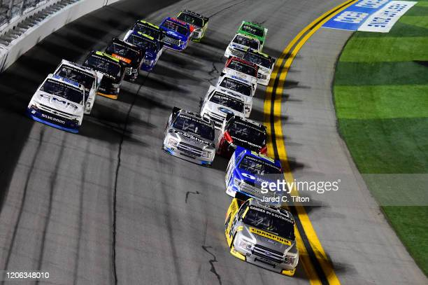 Grant Enfinger driver of the Champion/Curb Records Ford leads a pack of trucks during the NASCAR Gander RV Outdoors Truck Series NextEra Energy 250...