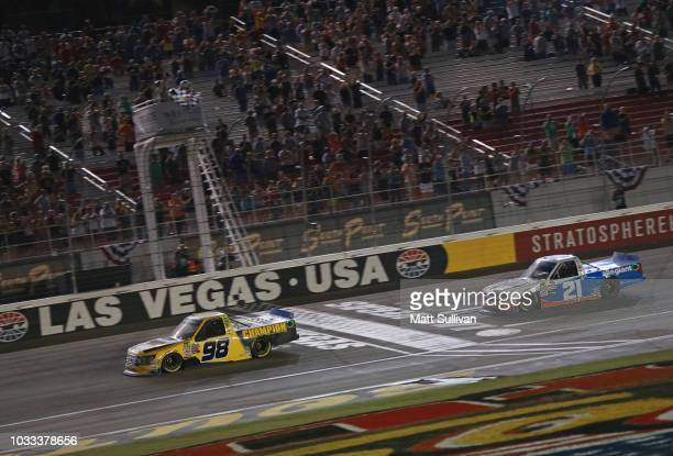 Grant Enfinger driver of the Ford takes the checkered flag in front of Johnny Sauter driver of the Allegiant Chevrolet to win the NASCAR Camping...