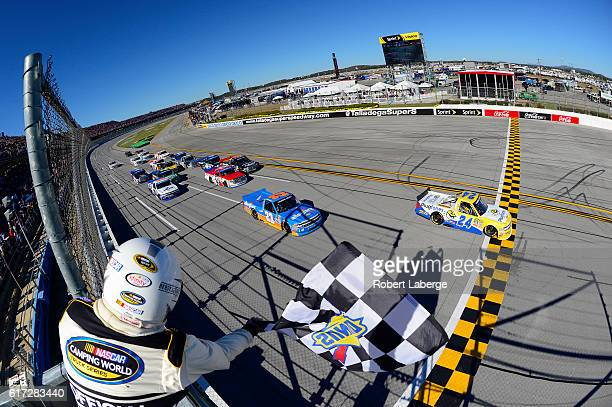 Grant Enfinger driver of the Plugfones Chevrolet takes the checkered flag to win the NASCAR Camping World Truck Series fred's 250 at Talladega...