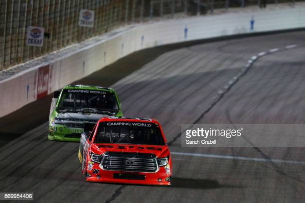 Grant Enfinger driver of the Ride TV Toyota leads Kaz Grala driver of the Stealth Chevrolet during the NASCAR Camping World Truck Series JAG Metals...