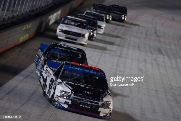 Grant Enfinger driver of the ThorSport Racing/Curb Records Ford leads a pack of trucks during the NASCAR Gander Outdoor Truck Series UNOH 200...