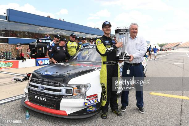 Grant Enfinger driver of the ThorSport Racing/Curb Records Ford receives the championship trophy from Scott Miller Senior VP of Competition after the...