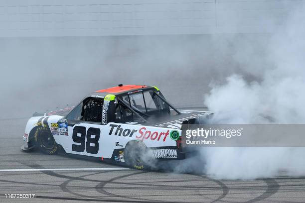 Grant Enfinger driver of the ThorSport Racing/Curb Records Ford celebrates with a burnout after winning the regular season championship at the NASCAR...