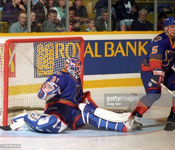 Grant Fuhr and Igor Kravchuk of the St Louis Blues skates against the Toronto Maple Leafs during NHL game action on December 3 1996 at Maple Leaf...