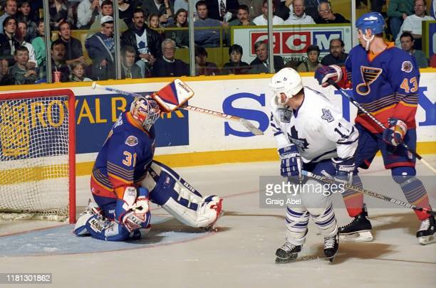 Grant Fuhr and Libor Zabransky of the St Louis Blues skate against Wendel Clark of the Toronto Maple Leafs during NHL game action on December 3 1996...
