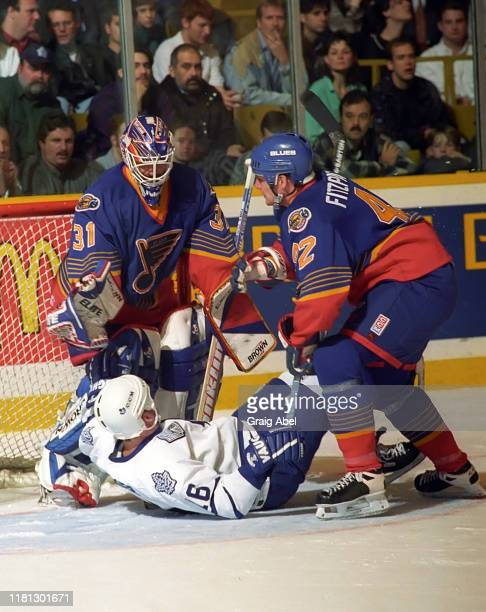 Grant Fuhr and Rory Fitzpatrick of the St Louis Blues skate against Jamie Baker of the Toronto Maple Leafs during NHL game action on December 3 1996...
