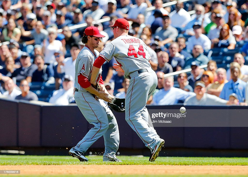 Grant Green #10 and Mark Trumbo #44 of the Los Angeles Angels of Anaheim collide and miss a ball hit for a third inning single by Alex Rodriguez #13 (not pictured) of the New York Yankees at Yankee Stadium on August 15, 2013 in the Bronx borough of New York City.
