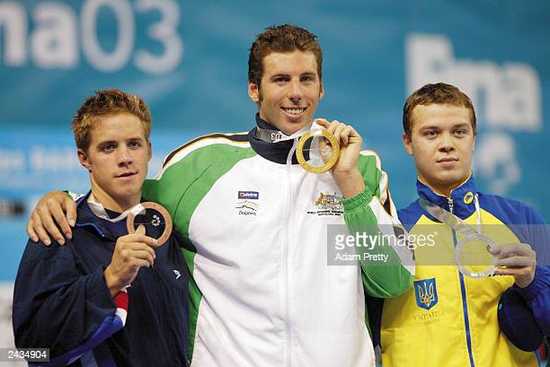 Grant Hackett of Australia displays his medal after winning gold with Igor Chervynskyi of Ukraine who won silver and Erik Vendt of the USA who won...