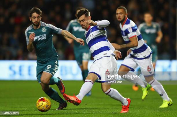 Grant Hall of QPR beats Will Grigg of Wigan Athletic to the ball during the Sky Bet Championship match between Queens Park Rangers and Wigan Athletic...