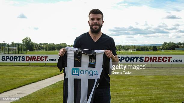 Grant Hanley poses for photographs holding a home shirt at the Newcastle United Training Centre on July 21 in Newcastle upon Tyne England
