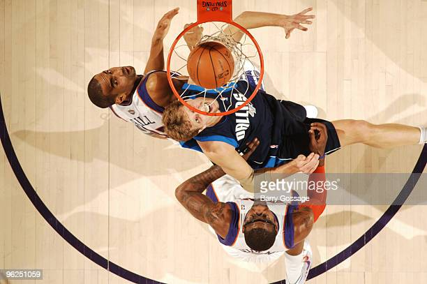 Grant Hill and Amare Stoudemire of the Phoenix Suns watch a basket drop by Dirk Nowitzki of the Dallas Mavericksin an NBA Game played on January 28...