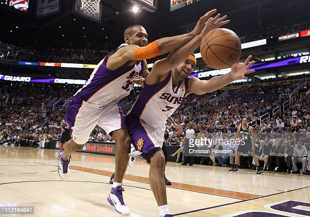Grant Hill and Jared Dudley of the Phoenix Suns reach for a loose ball during the NBA game against the San Antonio Spurs at US Airways Center on...