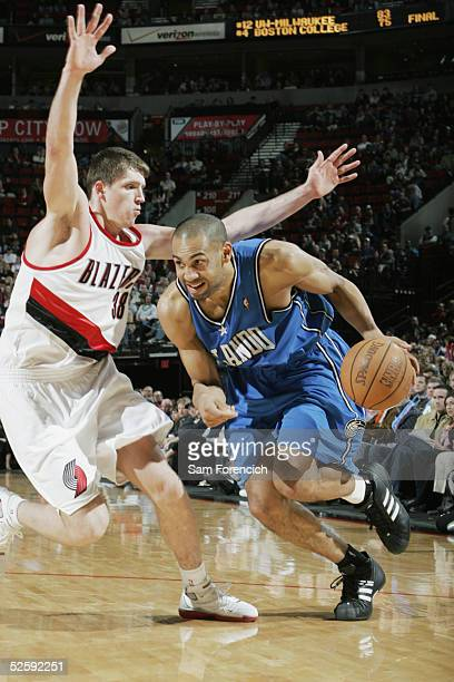 Grant Hill of Orlando Magic moves the ball against Viktor Khryapa of the Portland Trail Blazers share a laugh on the court during the game on March...
