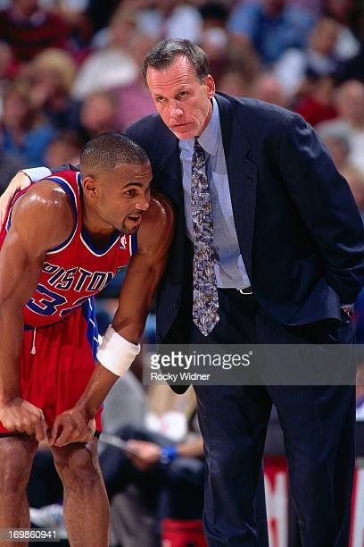 Grant Hill of the Detroit Pistons and Doug Collins talk against the Sacramento Kings during a game played on October 17 1996 at Arco Arena in...