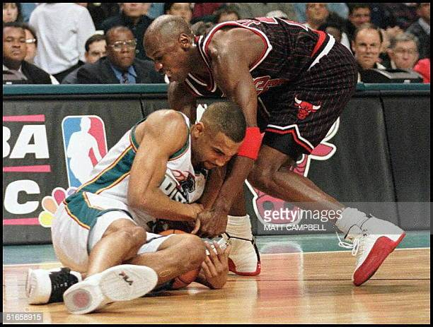 Grant Hill of the Detroit Pistons and Michael Jordan of the Chicago Bulls fight for a loose ball in the first quarter of their 13 April game at the...