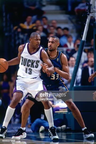 Grant Hill of the Detroit Pistons defends against Glenn Robinson of the Milwaukee Bucks during the game on November 18 1997 at the Bradley Center in...