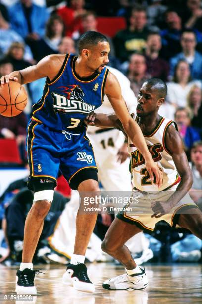 Grant Hill of the Detroit Pistons dribbles against Gary Payton of the Seattle SuperSonics during a game at the KeyArena at the Seattle Center in...