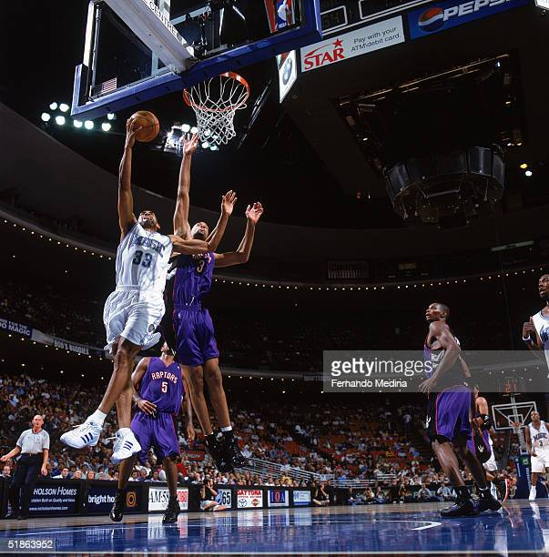Grant Hill of the Orlando Magic drives to the basket for a layup against Loren Woods of the Toronto Raptors during a game at TD Waterhouse Centre on...
