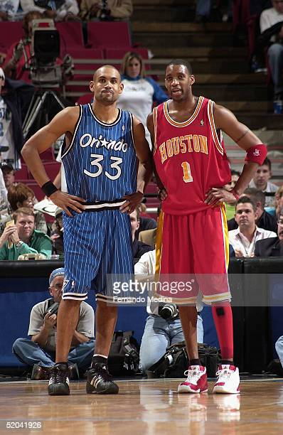 Grant Hill of the Orlando Magic stands next to former teammate Tracy McGrady the Houston Rockets at TD Waterhouse Centre on January 20 2005 in...