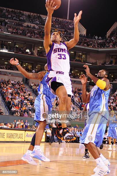 Grant Hill of the Phoenix Suns shoots against Nen� #31 of the Denver Nuggets in an NBA game played on October 11 at Indian Wells Tennis Garden in...