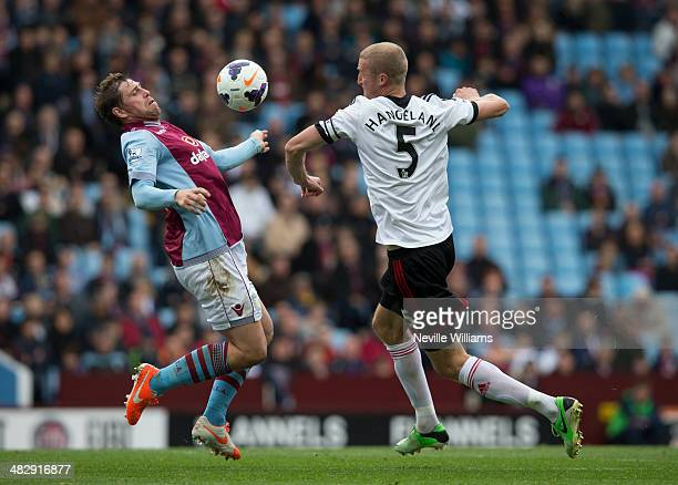 Grant Holt of Aston Villa is challenged by Brede Hangeland of Fulham during the Barclays Premier League match between Aston Villa and Fulham at Villa...