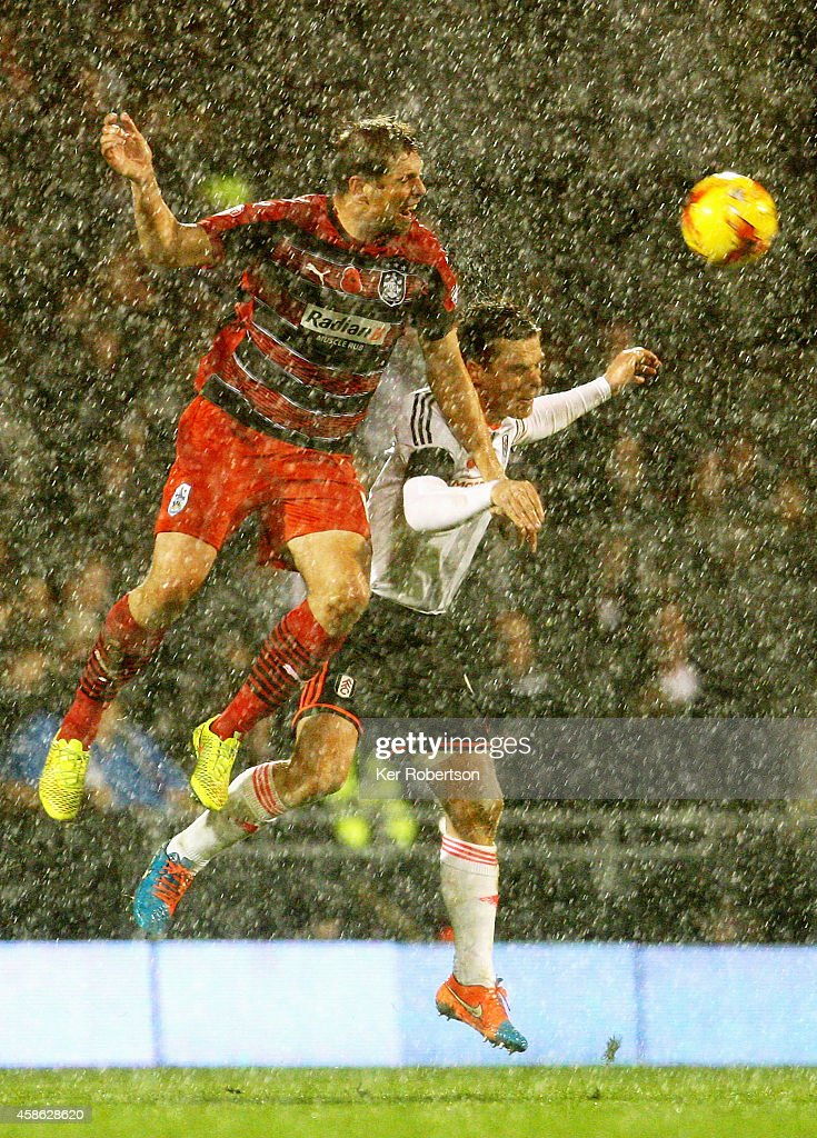 Grant Holt of Huddersfield Town and Scott Parker of Fulham challenge for the ball in the air during the Sky Bet Championship match between Fulham and Huddersfield Town at Craven Cottage on November 8, 2014 in London, England.