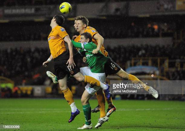 Grant Holt of Norwich City competes for a header with Christophe Berra and Stephen Ward of Wolves during the Barclays Premir League match between...