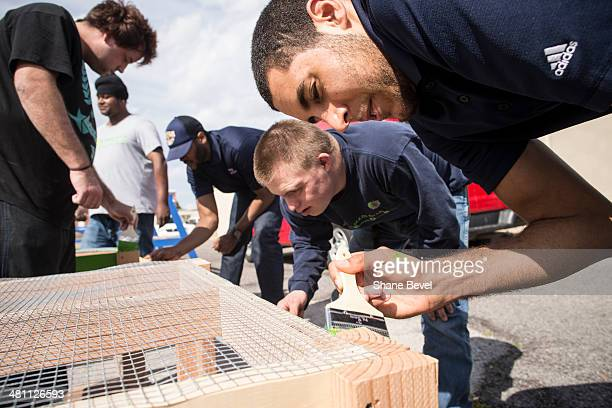 Grant Jerrett of the Tulsa 66ers helps Blake Nay paint a plant stand during the NBA DLeague community relations event at A New Leaf a nonprofit that...