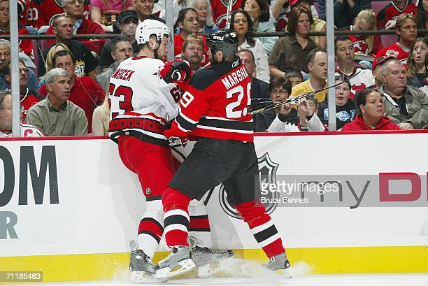 Grant Marshall of the New Jersey Devils battles Josef Vasicek of the Carolina Hurricanes along the boards in game three of the Eastern Conference...