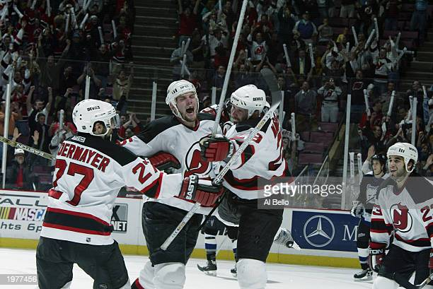 Grant Marshall of the New Jersey Devils celebrates the game winning goal with teammates Scott Niedermayer and Colin White against the Tampa Bay...