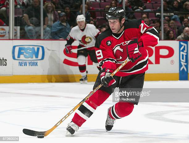 Grant Marshall of the New Jersey Devils skates with the puck against the Ottawa Senators during the NHL game at the Continental Airlines Arena on...