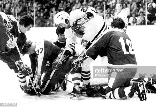 Grant Mulvey of the Chicago Blackhawks battles for the puck with Errol Thompson Darryl Sittler Ian Turnbull and Jim McKenny of the Toronto Maple...