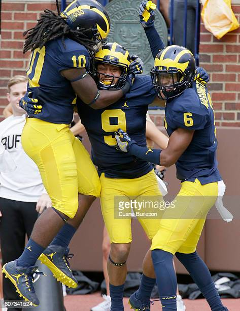 Grant Perry of the Michigan Wolverines celebrates with Devin Bush of the Michigan Wolverines and Keith Washington of the Michigan Wolverines after...
