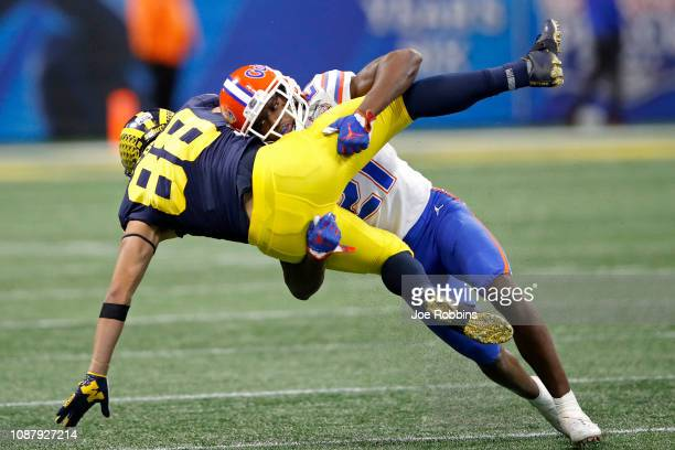 Grant Perry of the Michigan Wolverines is hit by Trey Dean III of the Florida Gators in the fourth quarter during the ChickfilA Peach Bowl at...