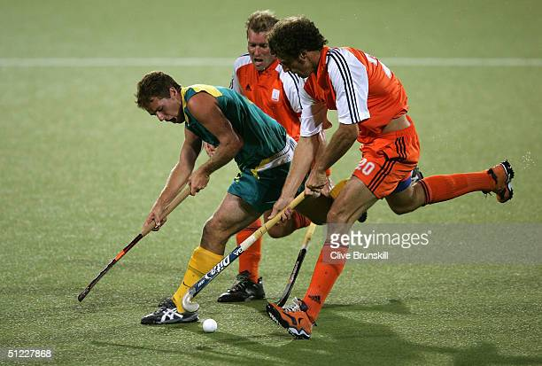 Grant Schubert of Australia dribbles against the defense of Jeroen Delmee and Jesse Mahieu of the Netherlands clash during the men's field hockey...
