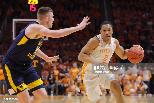 Grant Williams of the Tennessee Volunteers dribbles around Logan Routt of the West Virginia Mountaineers during their game at ThompsonBoling Arena on...