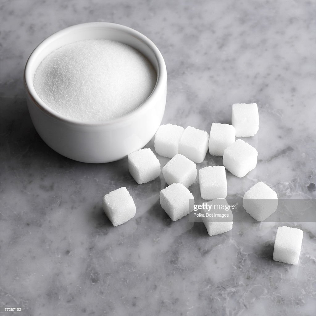 Granulated sugar in bowl with cubes on countertop : Stock Photo