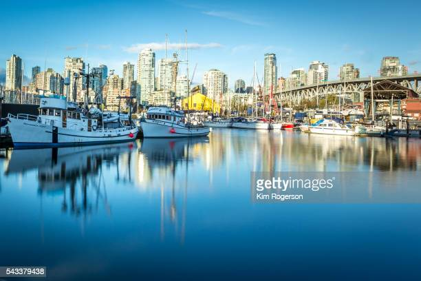 Granvile Island and boats with the Vancouver skyline as a backdrop.