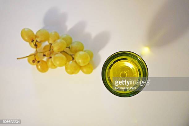 Grape and glass of wine on white surface