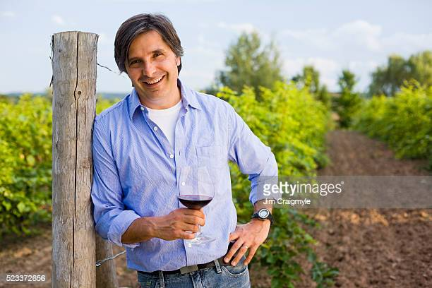grape farmer standing in a field with a glass of wine - jim farmer stock photos and pictures